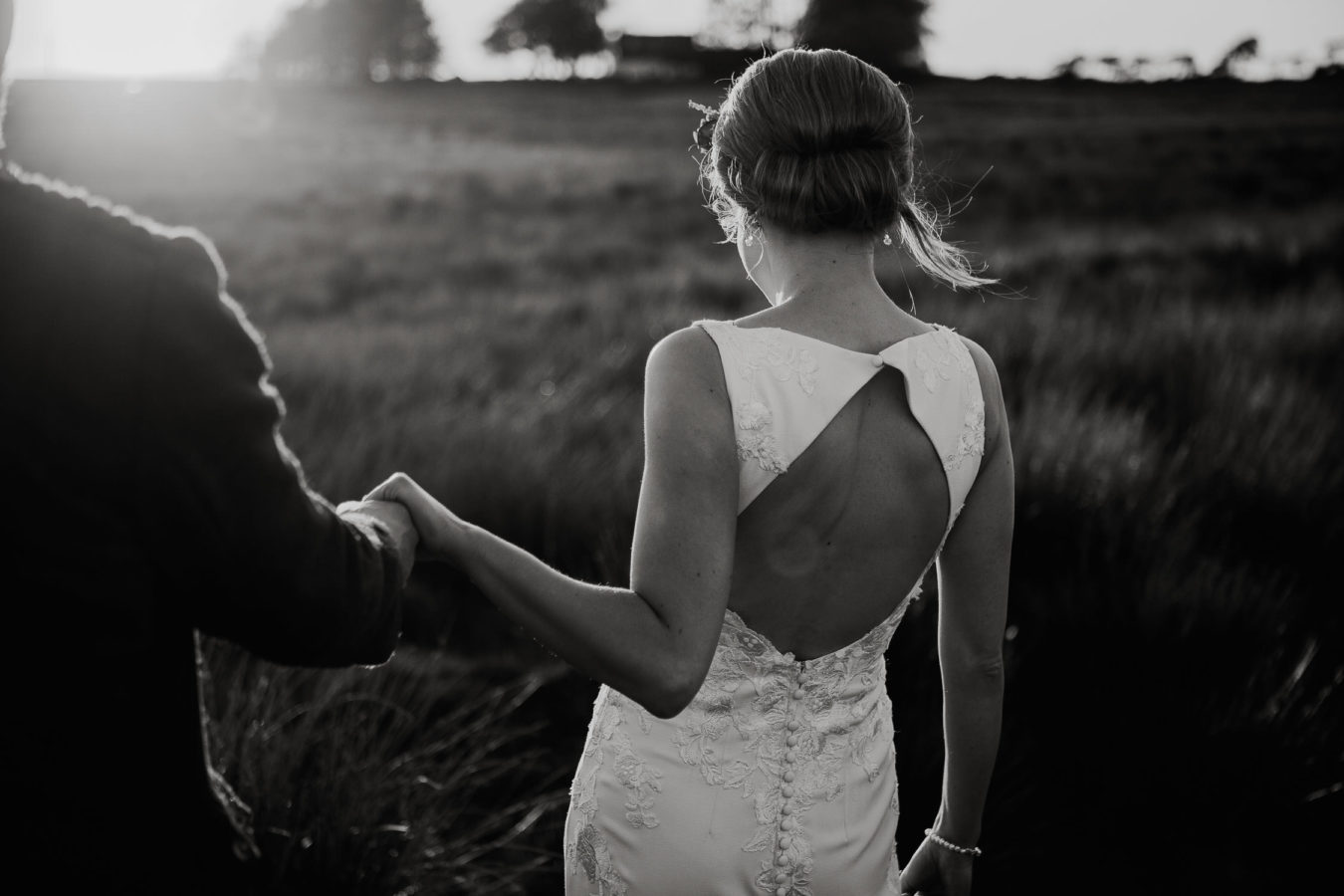 Bride holding grooms hand walking through field in black and white