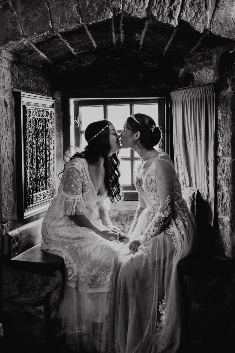 Brides kissing in window seat of Plane Castle in Stirling