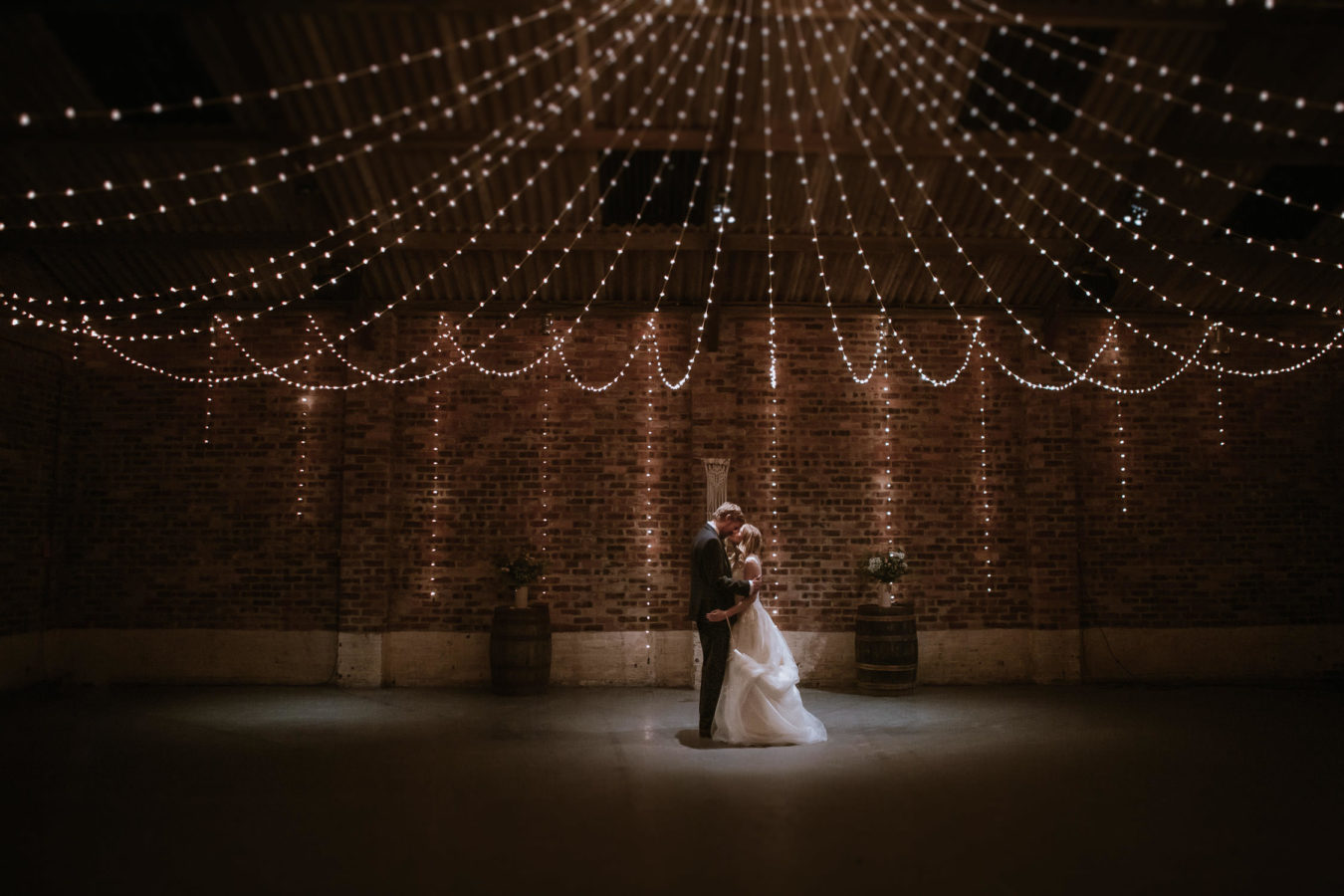 Bride and Groom hugging under canopy lighting inside Kinkell Byre Fife