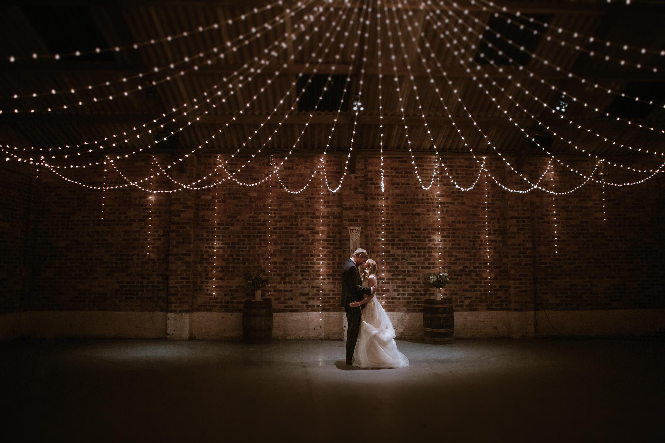 Bride and Groom hugging under canopy lighting inside Kinkell Byre Fife