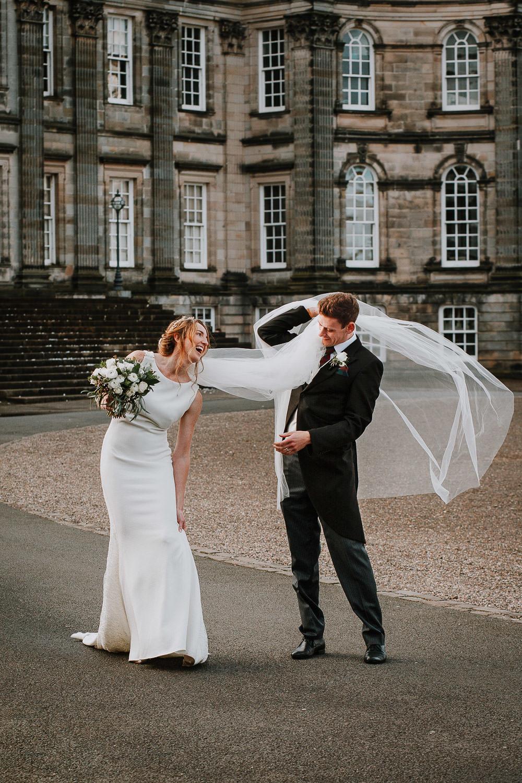 Groom caring brides veil over his shoulder at Hopetoun House Wedding