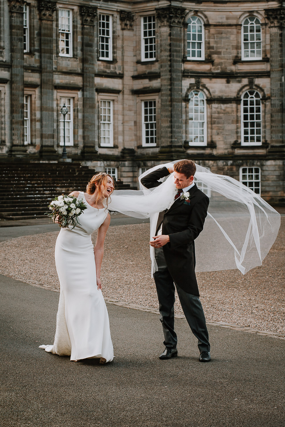 Groom caring brides veil over his shoulder at Hopetoun House Wedding