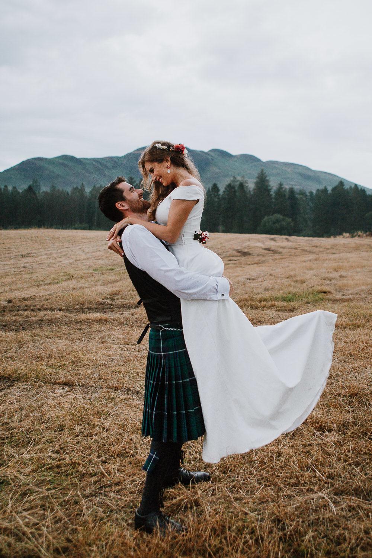 Groom lifting bride in the air in a field loch lomond