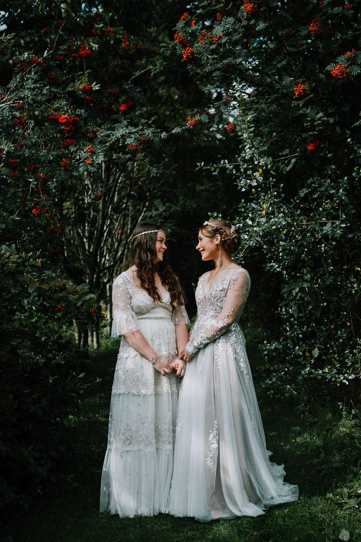 Brides holding hands under trees at Plane Castle Wedding