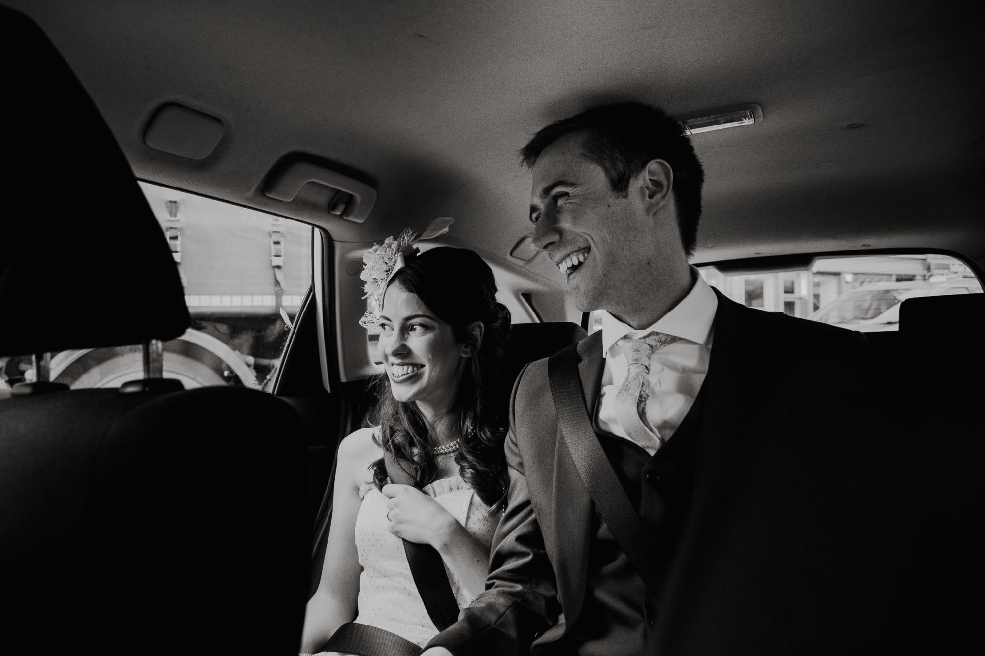 Black and white image of married couple in the back of a taxi